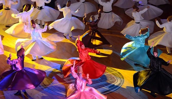 "BURSA, TURKEY - DECEMBER 13 :  Whirling dervishes perform  during the ""Seb-i Arus"" ceremony at Bursa Ataturk Gymnasium on December 13, 2013 in Bursa, to point the 740th anniversary of the death of Sufi mystic poet Mevlana. Seb-i  Arus is considered in Sufism to be reunited with God.  People aged between 7-42, are to perform around an hour during the Sema ceremony organized by Bursa Osmangazi Municipality. (Photo by Ali Atmaca /Anadolu Agency/Getty Images)"